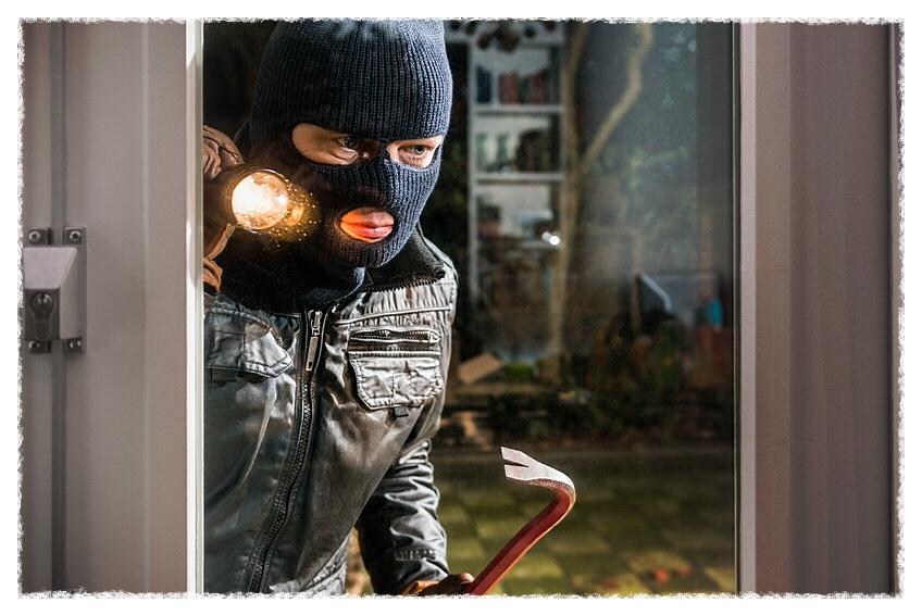 Burglar With Flashlight And Crowbar Looking Into Glass Window