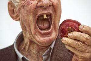 alter Mann beisst in den Apfel Zahngesundheit Halle